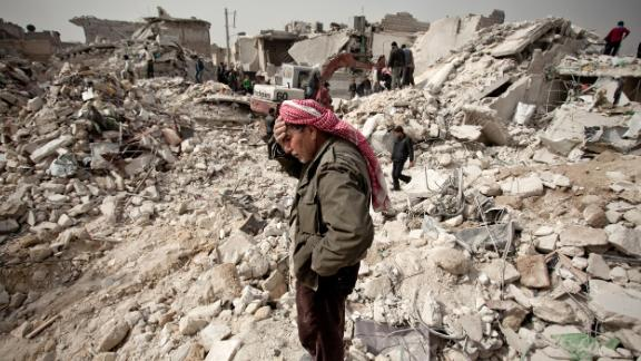 A Syrian man reacts while standing on the rubble of his house while others look for survivors and bodies in Aleppo.