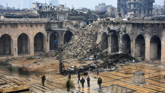 Syrian pro-government forces walking in the ancient Umayyad mosque in the old city of Aleppo after they captured the area.