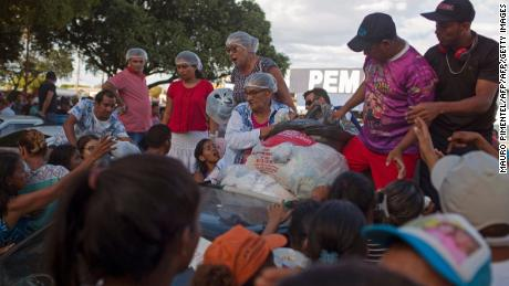Venezuelan refugees gather to receive clothes distributed by volunteers at the Simon Bolivar square in the city of Boa Vista, Roraima, Brazil, on February 25, 2018.  When the Venezuelan migratory flow exploded in 2017 the city of Boa Vista, the capital of the state of Roraima, 200 kilometers from the Venezuelan border, began to set up shelters as people started to settle in squares, parks and corners of this city of 330,000 inhabitants of which 10 percent is now Venezuelan.  / AFP PHOTO / Mauro PIMENTELMAURO PIMENTEL/AFP/Getty Images