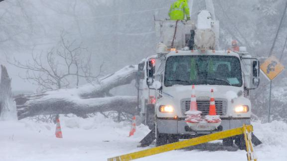 Workers remove a fallen tree from a road in Norwell, Massachusetts, on March 13.