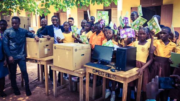 Richard Appiah Akoto (second from left) and his students show off their new computers and books.