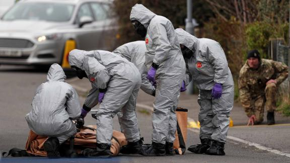 British military personnel wearing protective coveralls work to remove a vehicle connected to the March 4 nerve agent attack in Salisbury.