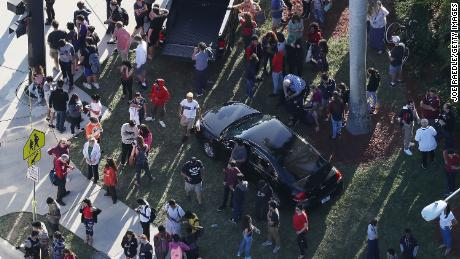 People wait for loved ones as they are brought out of the Marjory Stoneman Douglas High School after a shooting at the school that reportedly killed and injured multiple people on February 14, 2018 in Parkland, Florida.