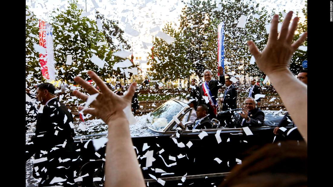 Chilean President Sebastian Piñera waves from a car as he makes his way to his inauguration on Sunday, March 11.