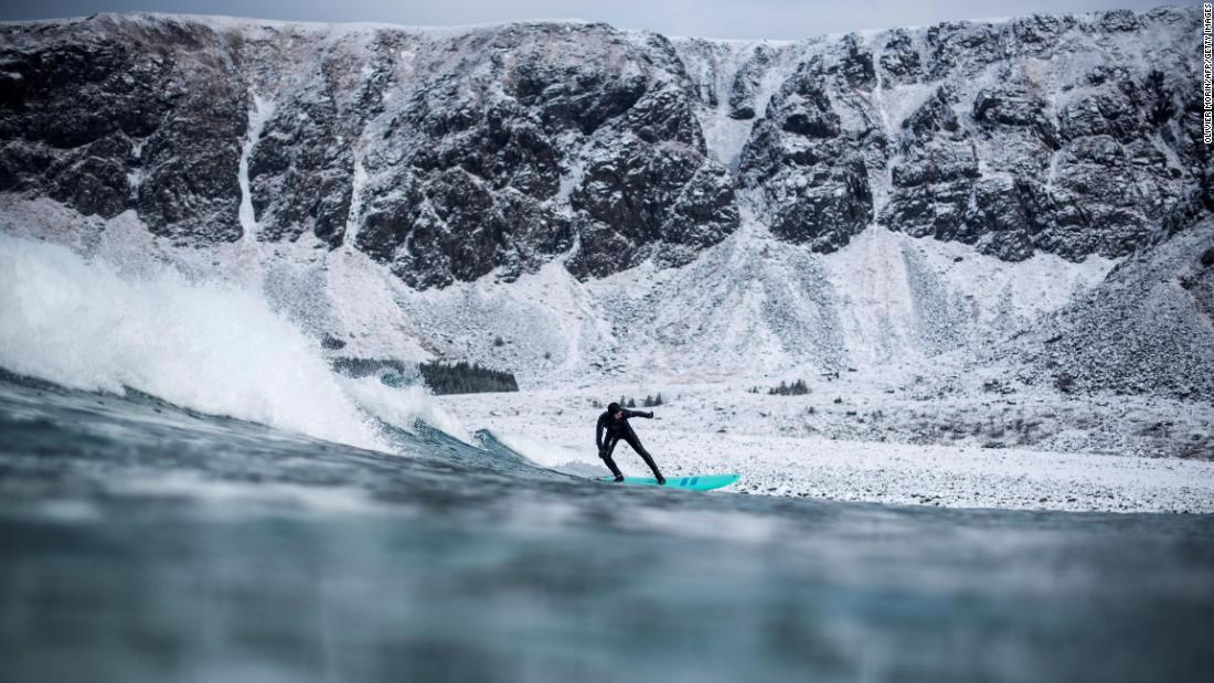 A surfer rides a wave in Unstad, Norway, on Saturday, March 10.