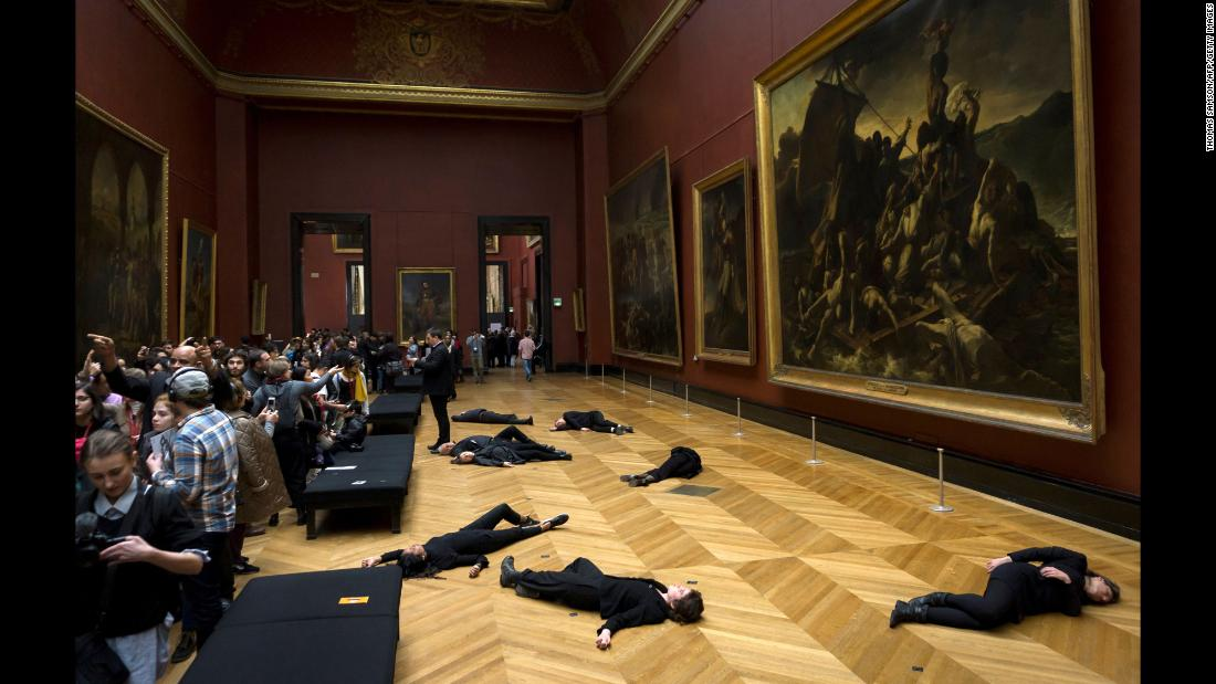 Members of the environmental activist group 350.org lie on the floor during a protest at the Louvre museum in Paris on Monday, March 12. The group was protesting the museum's sponsorship deal with the oil firm Total.