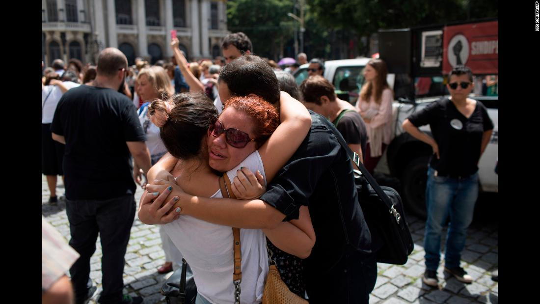 People console each other in front of Rio de Janeiro's City Hall as they pay their respects to city councilwoman Marielle Franco, who was gunned down while sitting in a car on Wednesday, March 14. Franco was 38.