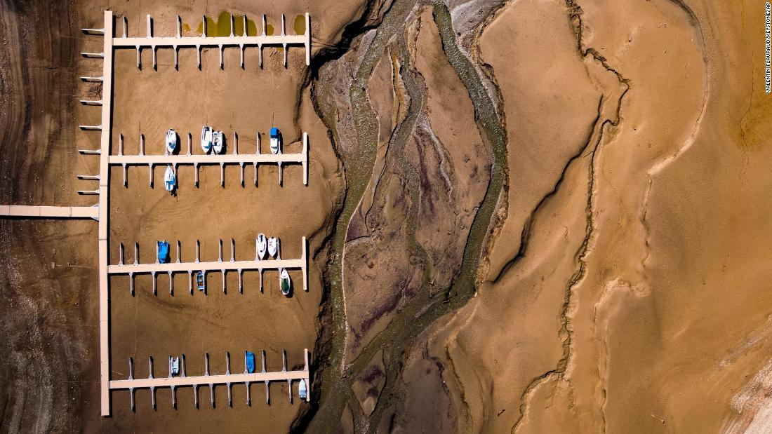 Stranded boats are seen on a dried-up shore of Switzerland's Lake of Gruyere on Wednesday, March 14. The artificial reservoir's water level is being reduced to make room for melting snow that will soon be coming from the surrounding mountains.
