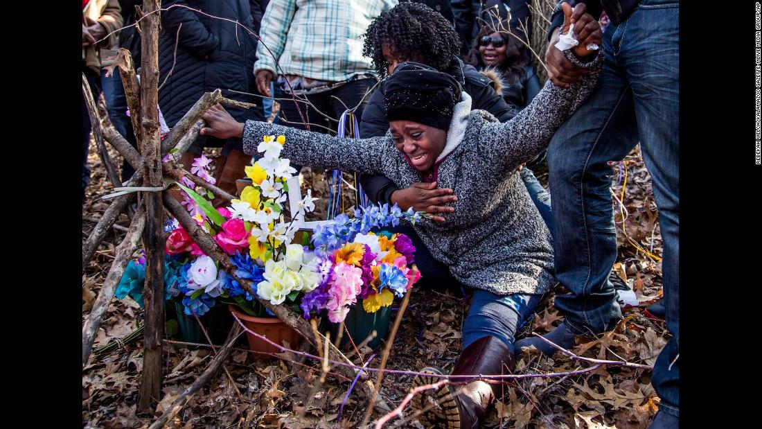 Fatmata Corneh cries at a memorial constructed for her daughter, Mujey Dumbuya, in Kalamazoo, Michigan, on Sunday, March 11. Mujey, 16, was found dead in Kalamazoo in January.