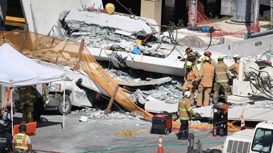 Rescue teams look for victims in cars trapped in the rubble.