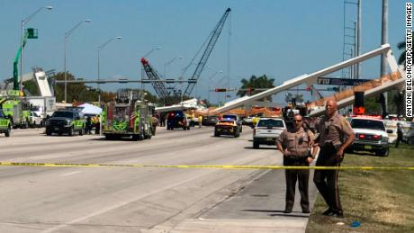Police block a road near a newly installed pedestrian bridge, that collapsed, over a six-lane highway in Miami, Florida on March 15, 2018, crushing a number of cars below and reportedly leaving several people dead. The Miami Herald reported that an unknown number of people were trapped underneath the collapsed walkway, which connected Florida International University to a student housing area and was erected less than a week ago. / AFP PHOTO / AFP TV / Antoni BELCHI        (Photo credit should read ANTONI BELCHI/AFP/Getty Images)