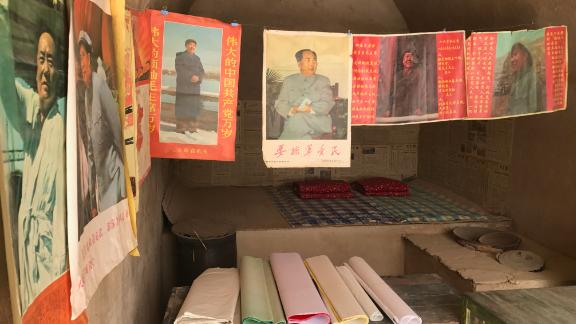 """Posters of Mao Zedong and other reproduced Cultural Revolution-era articles are on display in several """"cave houses"""" that Xi lived in the village."""