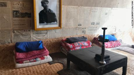 "A photo of a youthful Xi as well as old newspapers adorn the wall above his old shared bed in a ""cave house."""