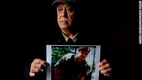 "Miguel Perez poses as he holds a photo of his son Miguel Perez Jr., on April 4, 2017 in Chicago, Illinois. Perez Jr., an Army veteran is facing deportation after serving seven years in a state penitentiary on a drug charge. / AFP PHOTO / Joshua LOTT / TO GO WITH AFP STORY BY NOVA SAFO-""US military veterans deported after committing crimes""        (Photo credit should read JOSHUA LOTT/AFP/Getty Images)"