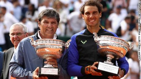 "Toni Nadal (left) holds up a replica ""Decima"" trophy after his nephew won a 10th French Open title in 2017."
