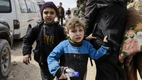 A Syrian girl and boy from the Eastern Ghouta enclave walk with another woman and civilians through the regime-controlled corridor opened by government forces in Hawsh al-Ashaari, east of the enclave town of Hamouria on the outskirts of the capital Damascus on March 15, 2018.Thousands escaped Syria