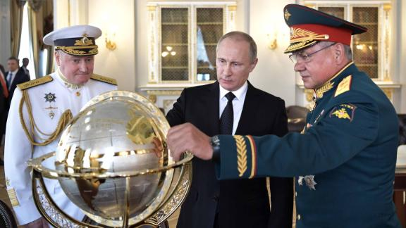 Russian President Vladimir Putin (C), Defence Minister Sergei Shoigu (R) and Commander in Chief of the Russian Navy Vladimir Korolev (L) watch a terrestrial globe while visiting Russia
