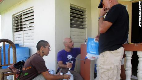 Volunteers Pablo Méndez Lázaro, Lenulisy Rosado and William Preston demonstrate water filtration to Montones residents.