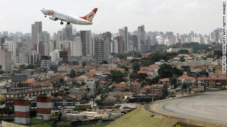 Sao Paulo, BRAZIL: With a city landscape behind, an aircraft of Brazilian airline Gol takes off from the Congonhas domestic airport in Sao Paulo, Brazil, 02 April 2007. On the weekend, airports struggled to get passengers back in the air after a strike by air traffic controllers who demanded systemic fixes since Brazil's worst air traffic disaster six months ago, killing 154 passengers. An hours-long air traffic controllers' strike, which ended late Friday, grounded 80 percent of air passenger traffic. Brazilian domestic airlines claiming losses of 48.5 million dollars in a six-month tussle with air traffic controllers sought compensation Sunday from the government.  AFP PHOTO/Mauricio LIMA (Photo credit should read MAURICIO LIMA/AFP/Getty Images)