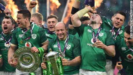 Ireland's hooker Rory Best (C) holds the Six Nations trophy and Ireland's fly-half Jonathan Sexton (2L) the Triple Crown as Ireland players celebrate their Six Nations Grand Slam victory after the Six Nations international rugby union match between England and Ireland at the Twickenham, west London, on March 17, 2018. / AFP PHOTO / Glyn KIRK        (Photo credit should read GLYN KIRK/AFP/Getty Images)