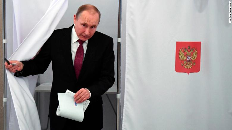 Russian President Vladimir Putin exits a polling booth as he prepares to cast his ballot during Russia's presidential election.