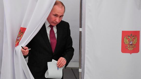 Russian President and Presidential candidate Vladimir Putin exits a polling booth as he prepares to cast his ballot during Russia