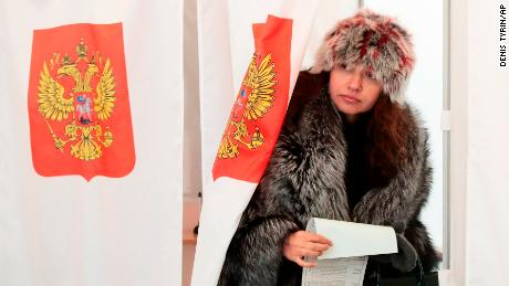 A woman exits a polling booth as she prepares to cast her ballot in the presidential election in Moscow, Sunday, March 18, 2018. Russians are voting in a presidential election in which Vladimir Putin is seeking a fourth term in the Kremlin. (AP Photo/Denis Tyrin)