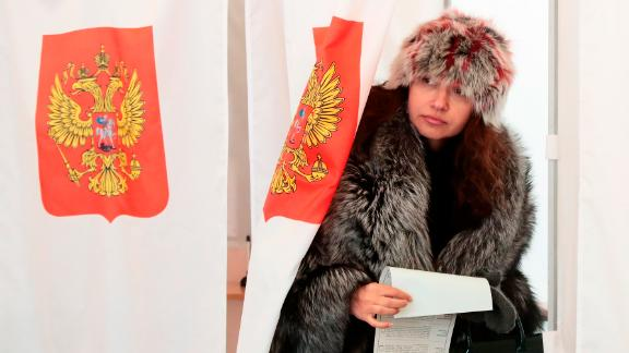A woman exits a polling booth as she prepares to cast her ballot in the presidential election in Moscow.