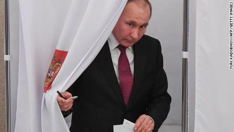 Presidential candidate Vladimir Putin walks out of a voting booth at a polling station during Russia's presidential election in Moscow on March 18.