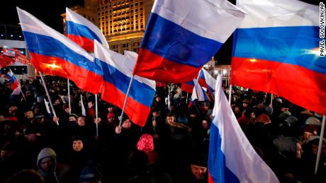 People wave Russian flags in Manezhnaya Square near the Kremlin on Sunday.