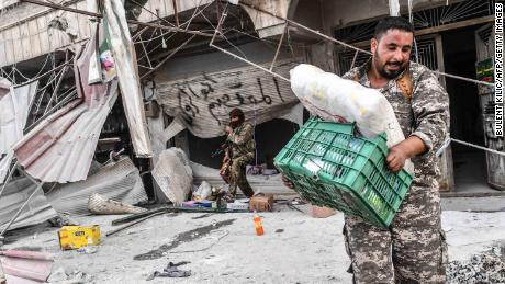 TOPSHOT - Turkish-backed Syrian Arab fighters loot shops after seizing control of the northwestern Syrian city of Afrin from the Kurdish People's Protection Units (YPG) on March 18, 2018.