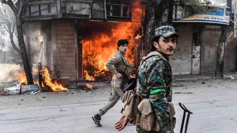 Rebel fighters walk past a burning shop in Afrin.
