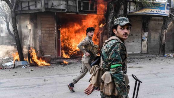 Turkish-backed Syrian rebels walk past a burning shop in the city of Afrin in northern Syria on March 18, 2018.