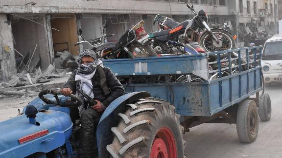 A fighter tows looted items in a trailer.