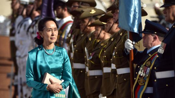 Myanmar's State Counsellor Aung San Suu Kyi (L) receives an official welcome on the forecourt during her visit to Parliament House in Canberra on March 19, 2018. Suu Kyi is in the Australian capital after attending the ASEAN (Association of Southeast Asian Nations)-Australia special summit in Sydney over the weekend. / AFP PHOTO / MARK GRAHAM        (Photo credit should read MARK GRAHAM/AFP/Getty Images)