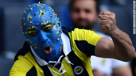 TOPSHOT - A Fenerbahce fan cheers his team before the Turkish Super Lig football match between Fenerbahce and Galatasaray on March 17, 2018, at the Fenerbahce Ulker Stadium in Istanbul. / AFP PHOTO / OZAN KOSE        (Photo credit should read OZAN KOSE/AFP/Getty Images)