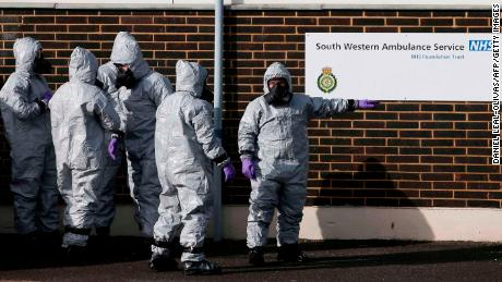 Personnel in protective coveralls and breathing equiptment cover an ambulance with a tarpaulin at the Salisbury District Hospital in Salisbury, southern England, on March 10, 2018, in connection with the major incident sparked after a man and a woman were apparently poisoned in a nerve agent attack.