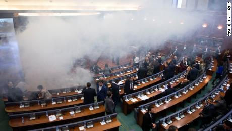 Kosovo lawmakers leave as smoke fills the auditorium of the Kosovo assembly after opposition lawmakers released tear gas canisters disrupting a parliamentary session in Kosovo capital Pristina on Wednesday, March 21, 2018. Kosovo's Parliament, has temporarily suspended its session after tear gas disrupted the vote on a border demarcation deal with Montenegro. (AP Photo/Visar Kryeziu)