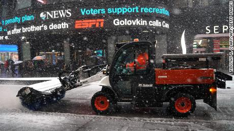 Workers in New York's Times Square battle the fourth nor'easter in a month Wednesday.