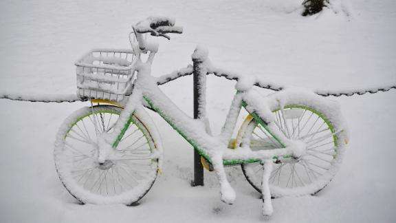 Snow covers a LimeBike rental bicycle Wednesday in Washington.