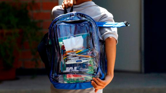 "A secondary school student walks carrying a new transparent backpack in Guadalajara, Mexico on October 25, 2012. The transparent backpacks are part of the program ""Escuela Segura"" (Safe School ) to avoid violence in schools."