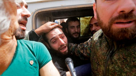 A vehicle carries civilians and soldiers whom the regime says were kidnapped by rebels and liberated.