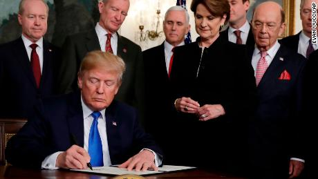 President Donald Trump signs a presidential memorandum imposing tariffs and investment restrictions on China in the Diplomatic Reception Room of the White House, Thursday, March 22, 2018, in Washington.