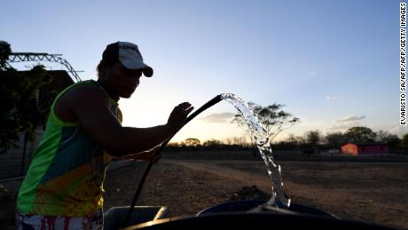A man fills barrels with water in the rural area of Quixeramobim, in Ceara State, on February 8, 2017, during the worst drought in a century in the Brazilian Northeast.  / AFP / EVARISTO SA / TO GO WITH AFP STORY BY CAROLA SOLE        (Photo credit should read EVARISTO SA/AFP/Getty Images)