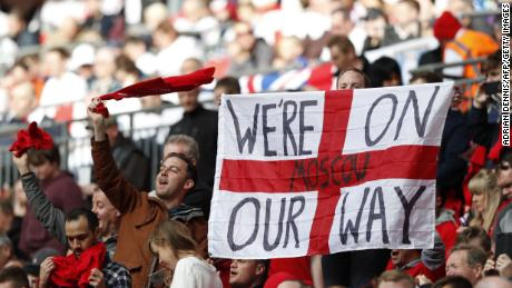 "England supporters hold up a ""we're on our way"" slogan on an England flag in the crowd ahead of the World Cup 2018 qualification football match between England and Lithuania at Wembley Stadium in London on March 26, 2017."