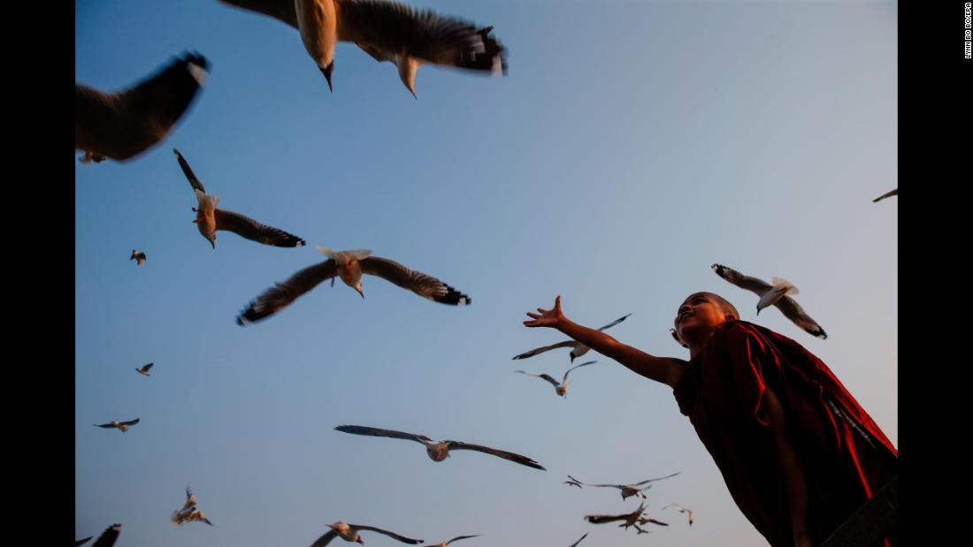 A young boy enjoys the evening as gulls fly overhead in Yangon, Myanmar, on Tuesday, March 20.