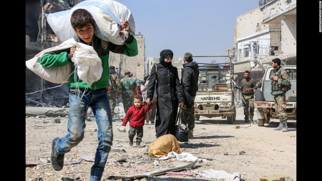 "A Syrian boy evacuates with other civilians from the town of Jisreen in Damascus, Syria, on Saturday, March 17. <a href=""https://www.cnn.com/2018/03/17/middleeast/syria-ghouta-evacuations-afrin-hospital/index.html"" target=""_blank"">Airstrikes rained down again</a> Saturday in Eastern Ghouta, according to activist group Damascus Media Center, as swarms of civilians continued to pour out of the battered rebel-held area not far from the nation's capital."