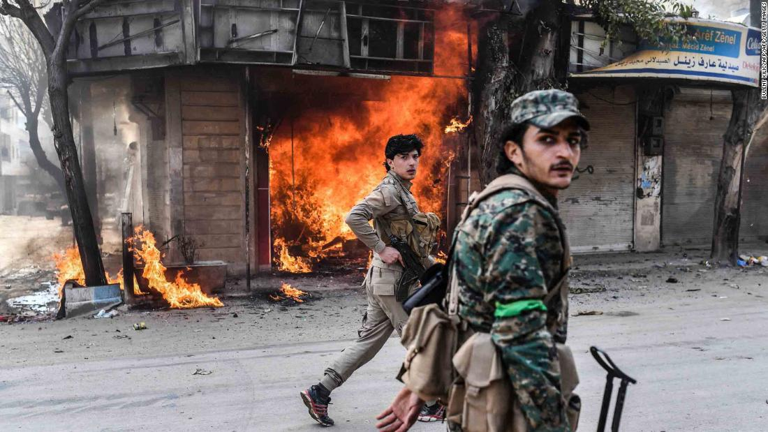 "Turkish-backed Syrian rebels walk past a burning shop in the city of Afrin in northern Syria on Sunday, March 18. Syrian rebel fighters backed by Turkey went on a looting spree in Afrin on Sunday after seizing control of the Kurdish-held town following a two-month siege, <a href=""https://www.cnn.com/2018/03/19/middleeast/afrin-looting-intl/index.html"" target=""_blank"">observers said</a>."
