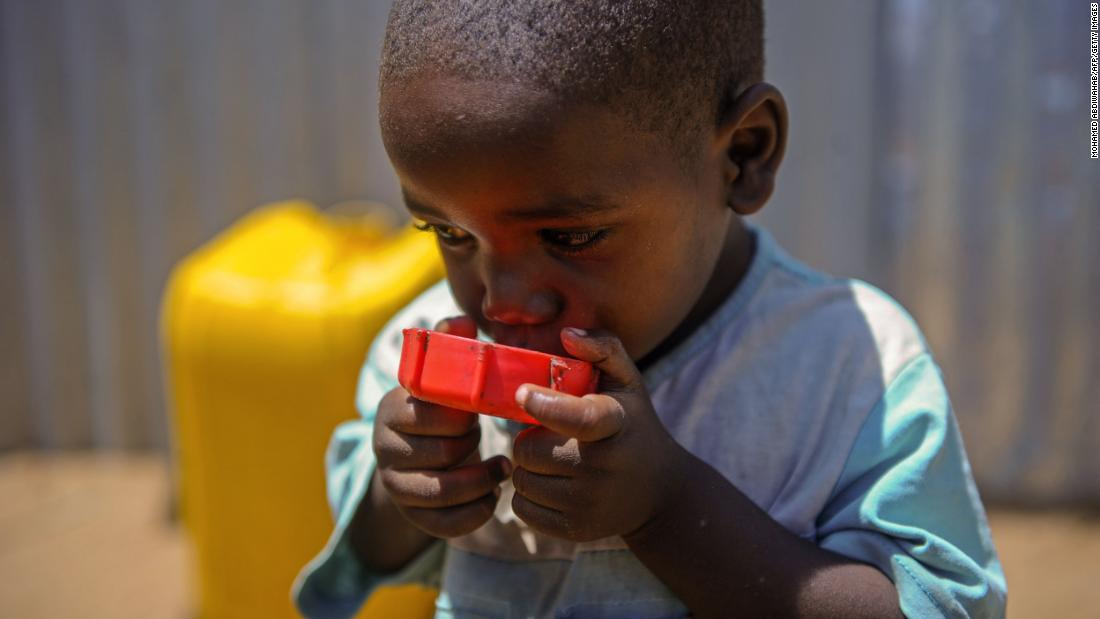A Somali child drinks water from a cap at the Tawakal IDP camp on the outskirts of Mogadishu, Somalia, on Wednesday, March, 21.