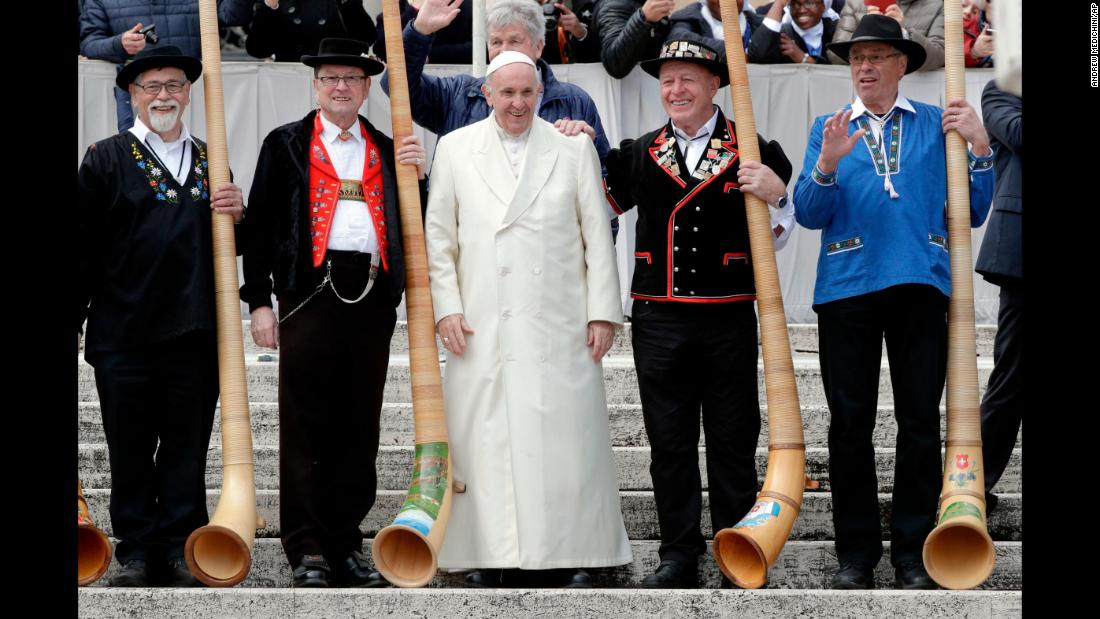Pope Francis poses for photos with a group of traditional Swiss horn players during his weekly general audience in St. Peter's Square at the Vatican on Wednesday, March 21.